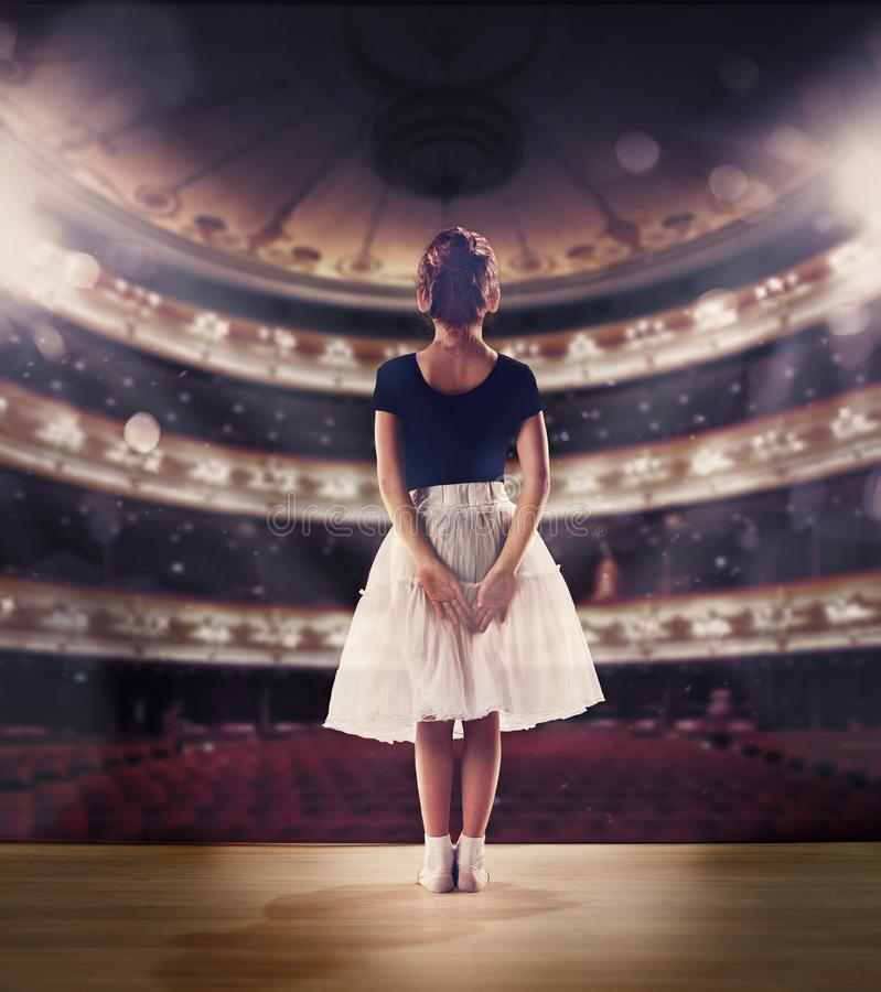 Baby girl dreaming a dancing ballet on the stage. Childhood concept. stock photos