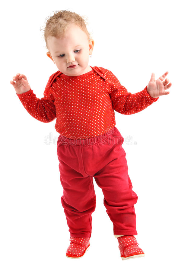 Baby girl dressed in red learning to walk isolated royalty free stock images
