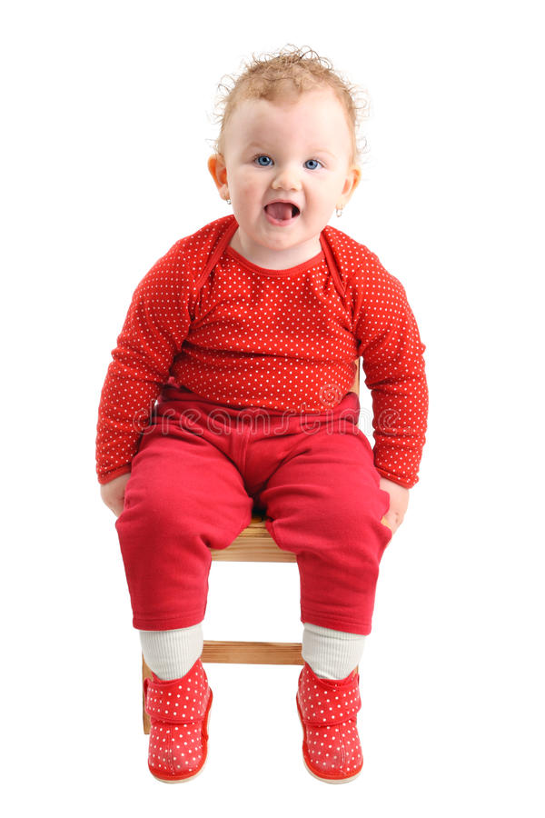 Baby girl dressed in red sitting on chair looking stock photo