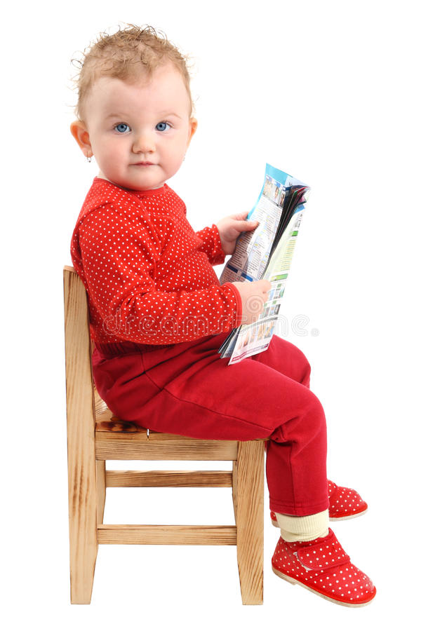 Baby girl dressed in red sitting on chair reading stock image