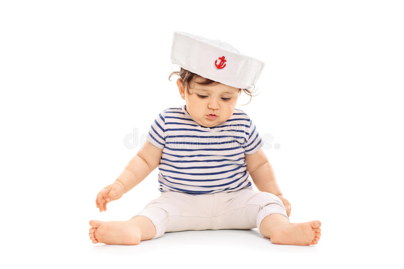 Baby girl dressed in sailor outfit sitting on the floor. Baby girl dressed in a sailor outfit sitting on the floor isolated on white background stock photos