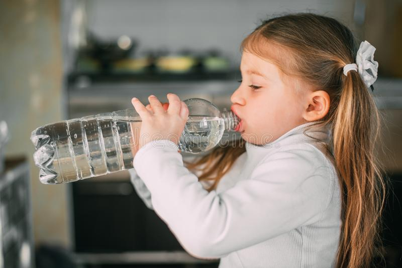Baby girl drinking greedily water from a plastic bottle with a volume of one liter royalty free stock photography