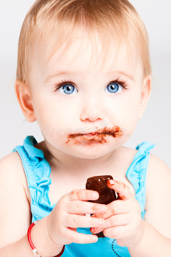 Download Baby girl eat chocolate stock image. Image of expression - 20976221