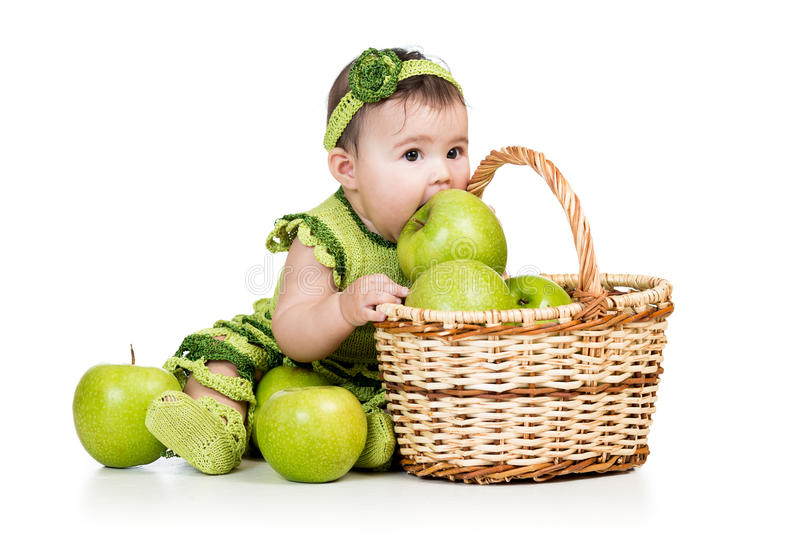 Baby girl eating green apples from basket royalty free stock photography
