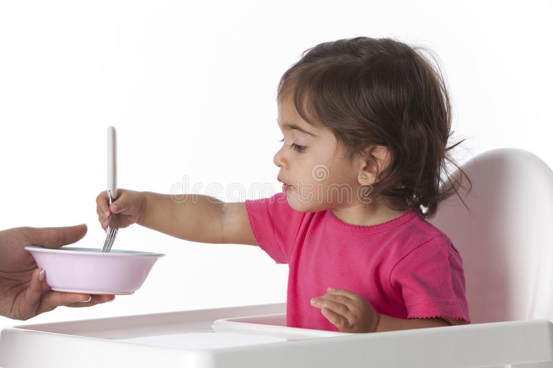 Baby girl is eating by herself with a fork