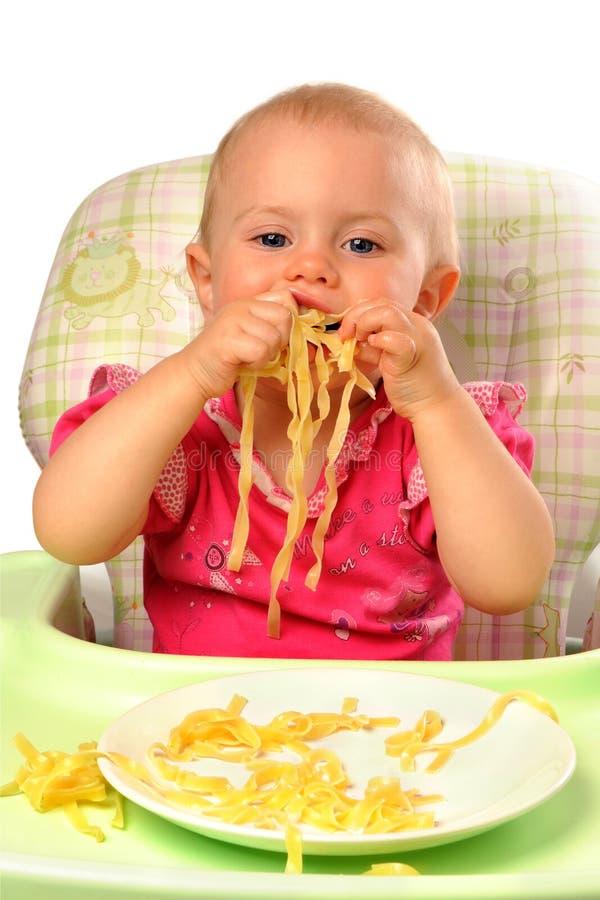 Baby girl eating pasta royalty free stock photo