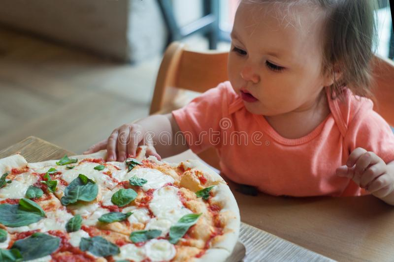 Baby girl eating pizza in italian restaurant, Healthy, unhealthy food, children`s fast food. royalty free stock photo