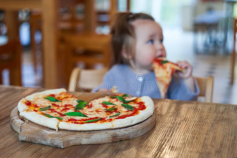 Baby girl eating pizza in italian restaurant, Healthy, unhealthy food, children`s fast food. royalty free stock photography