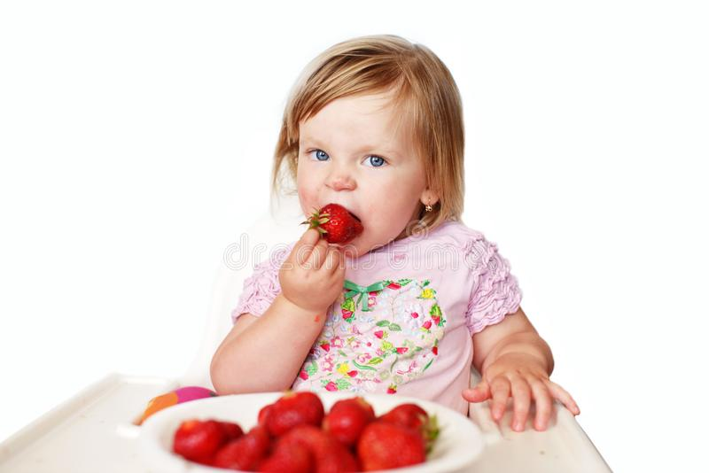 Baby  girl eating strawberry royalty free stock images