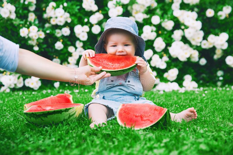 Baby girl eating watermelon on green grass in summertime on nature. Cutest smiling baby girl eating watermelon on green grass in summertime. Funny happy little stock images