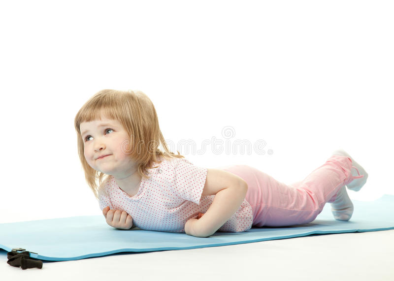 Baby girl exercising lying on a training mat. Pretty baby girl exercising lying on a training mat; white background stock photography