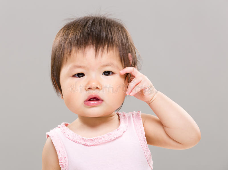 Baby girl feeling confuse. With gray background stock images