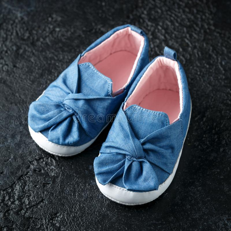 Baby girl first blue denim shoes with bow royalty free stock photo