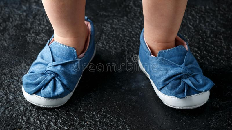 Baby girl first blue denim shoes with bow royalty free stock photography