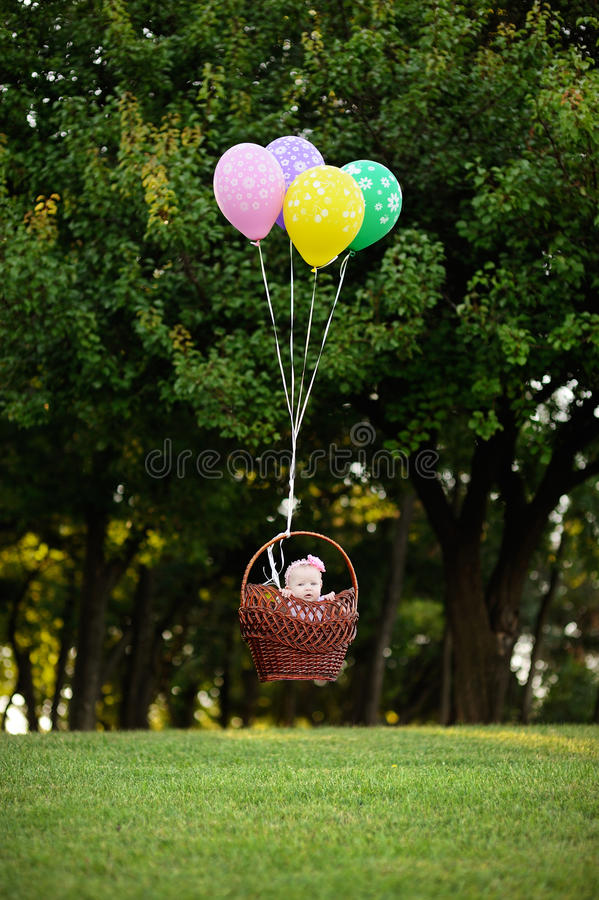 Baby girl flying in a basket on the balloons on a background of. Green trees stock images
