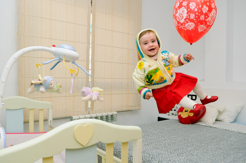 Baby girl flying with a red balloon in her bedroom stock photos