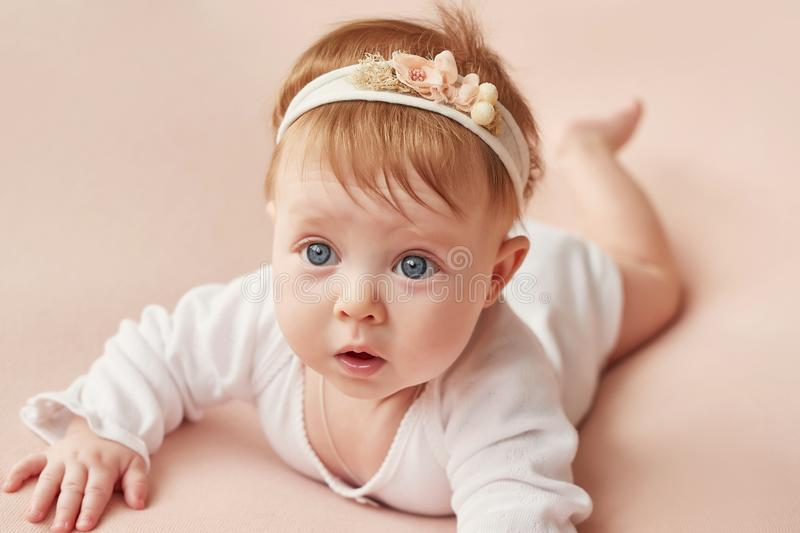 Baby girl of four months. Lies on a light pink background royalty free stock image