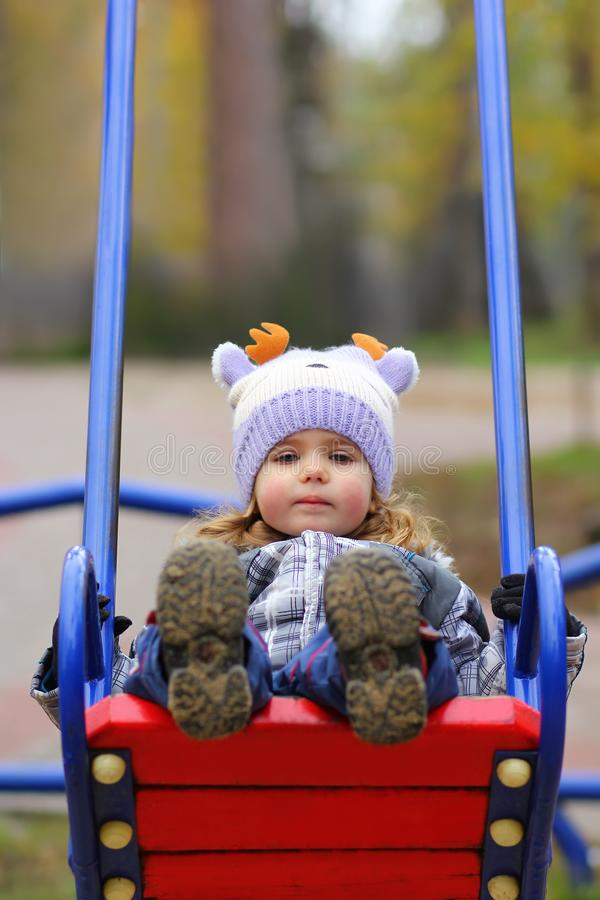 Baby girl in a funny hat swinging on the winter playground, perspective point of view. stock image