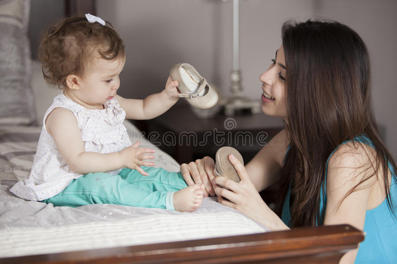Baby girl getting dressed. Young mom getting her baby girl dressed stock photography