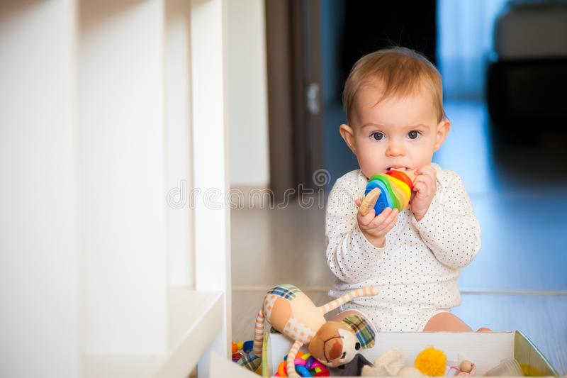 Baby girl gnawing a wooden colorful toy. Cute baby girl gnawing a wooden colorful toy royalty free stock photo