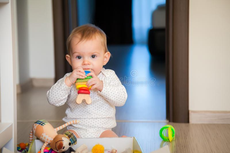 Baby girl gnawing a wooden toy. Adorable baby girl gnawing a wooden toy royalty free stock photography