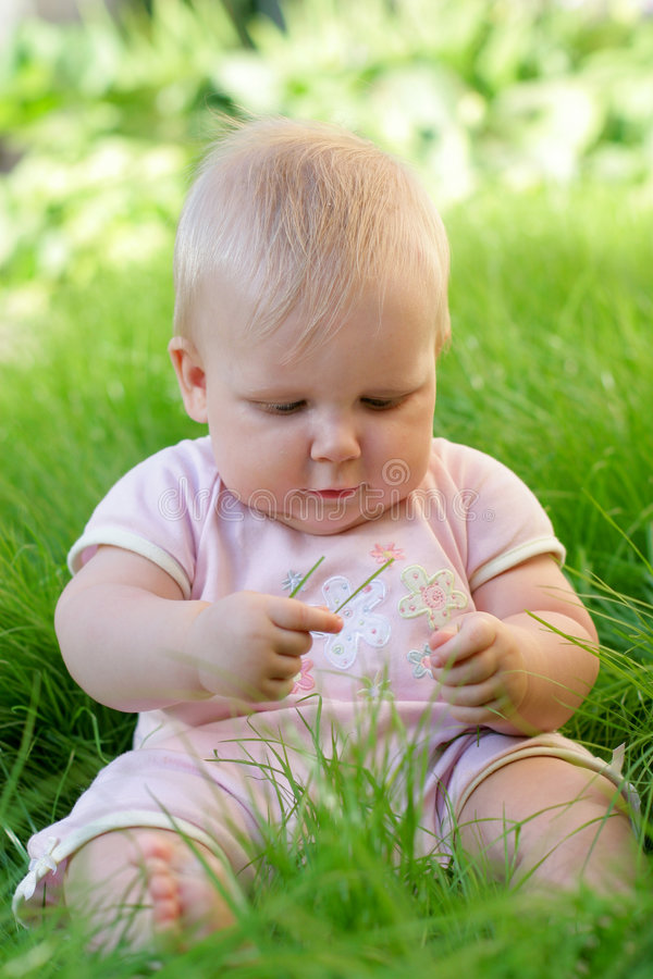 Baby girl in grass stock images