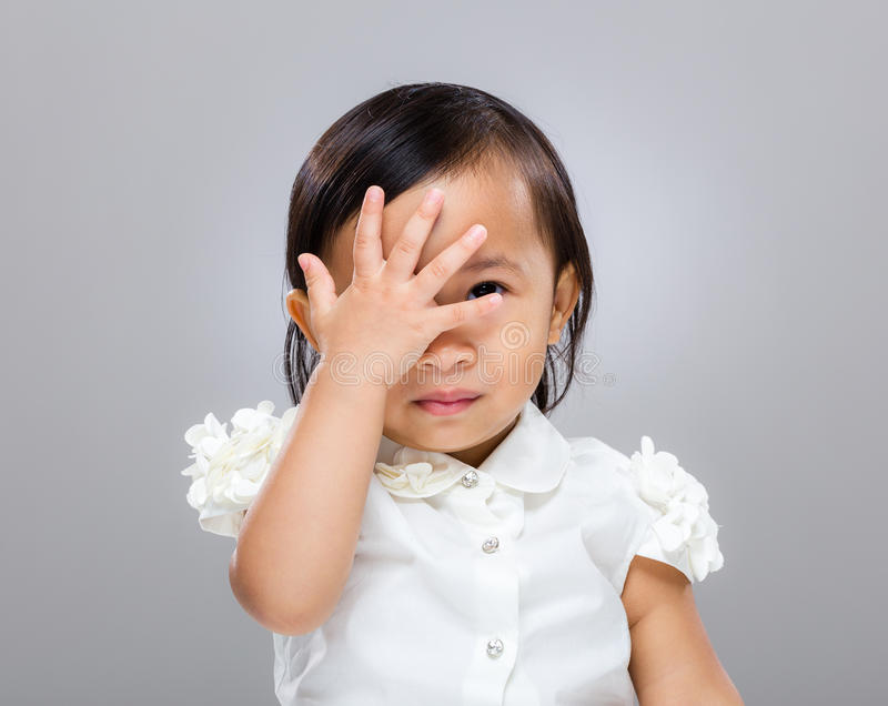 Baby girl with hand cover her face stock images