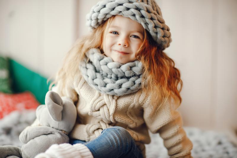 Baby girl in knitted hat and scarf. Baby girl a hand made knitted hat and scarf royalty free stock photography
