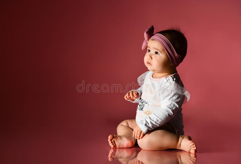 Baby girl in headband, smart white bodysuit, barefoot. She sitting on floor against pink background. New Year, holidays. Close up royalty free stock photo