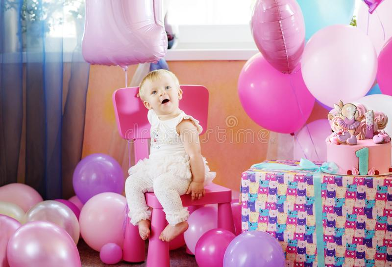Baby girl in her first birthday. With balloons and cake stock images