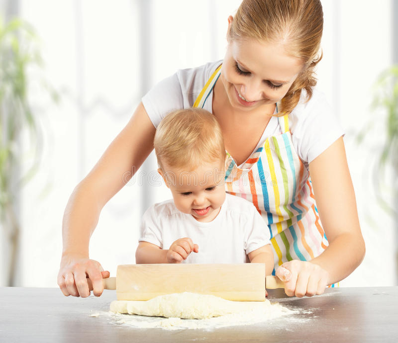 Baby girl with her mother cook, bake. Baby girl with her mother rolled out the dough cook, bake royalty free stock photo