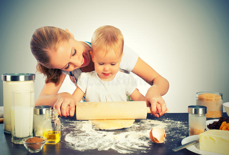 Baby girl with her mother cook, bake stock photography