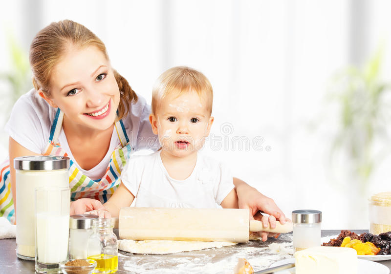 Baby girl with her mother cook, bake. Baby girl with her mother rolled out the dough cook, bake royalty free stock photos