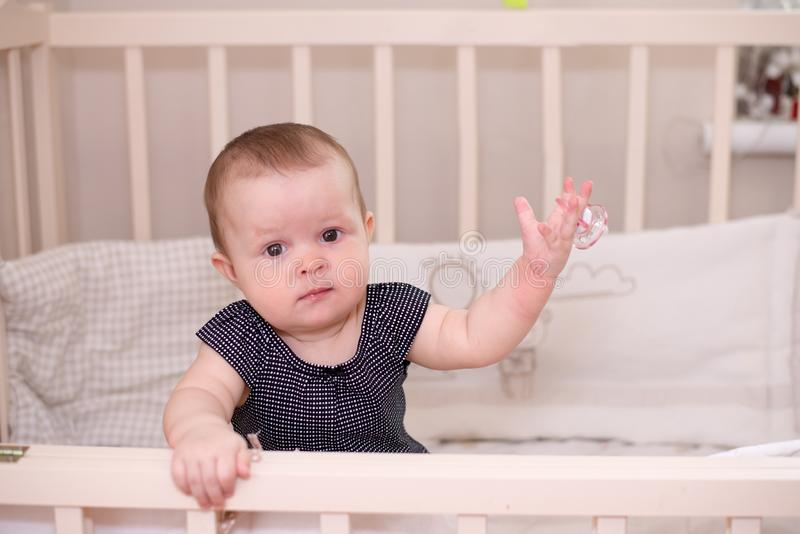 Baby girl with her pacifier posing in her bed stock photo
