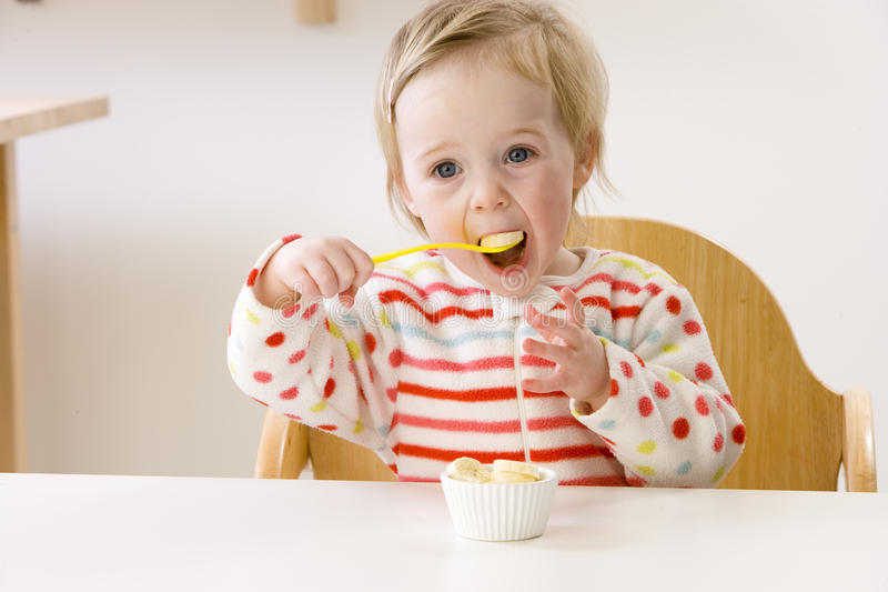 Baby girl in high chair eating banana slices.  royalty free stock image