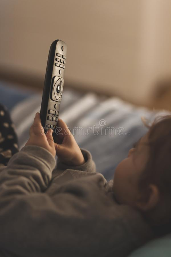 Baby girl hold TV remote control royalty free stock images