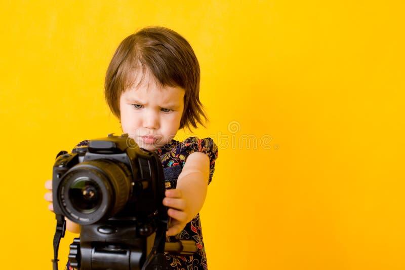 Baby girl holding photo camera