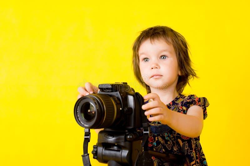 Baby girl holding photo camera stock photography