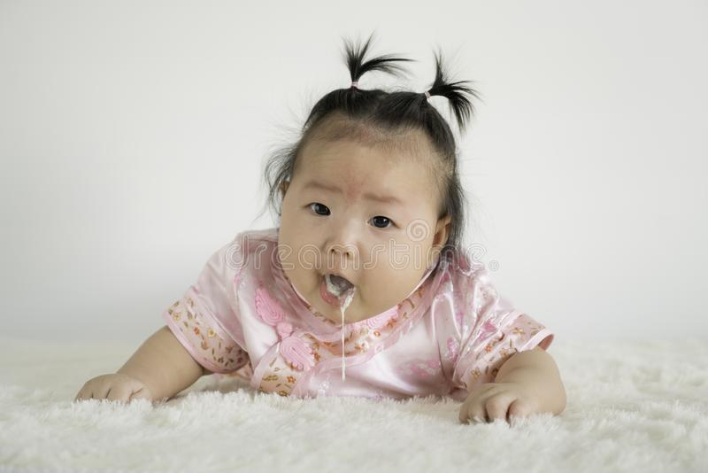 Baby girl Infant four months vomiting milk. Baby girl with a birthmark, birthmark on his forehead royalty free stock image