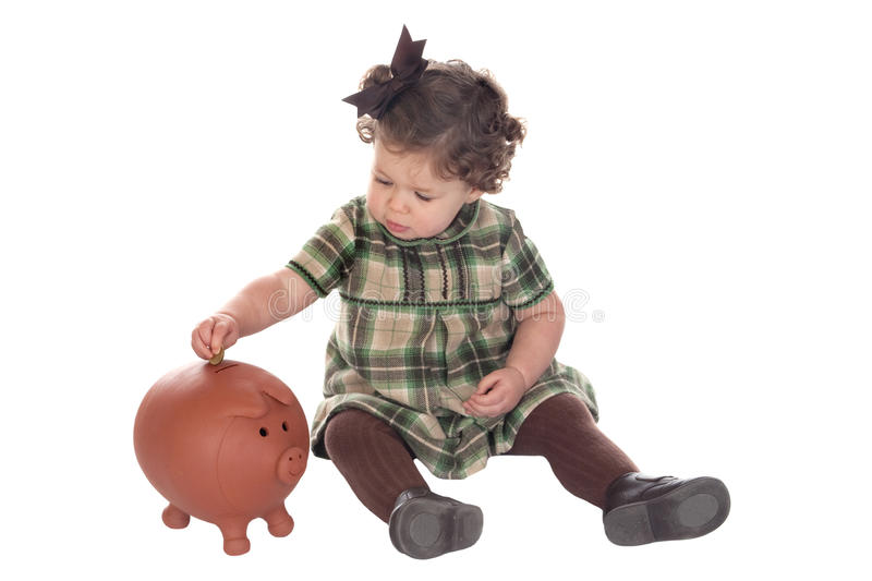 Baby Girl Inserting A Coin Into A Piggybank Royalty Free Stock Images