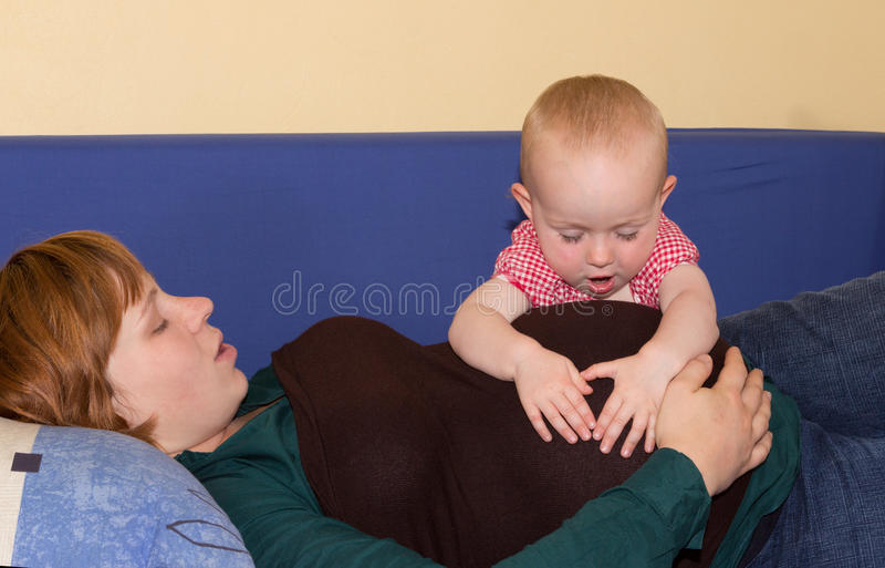 Baby girl investing her pregnant mothers belly stock photo