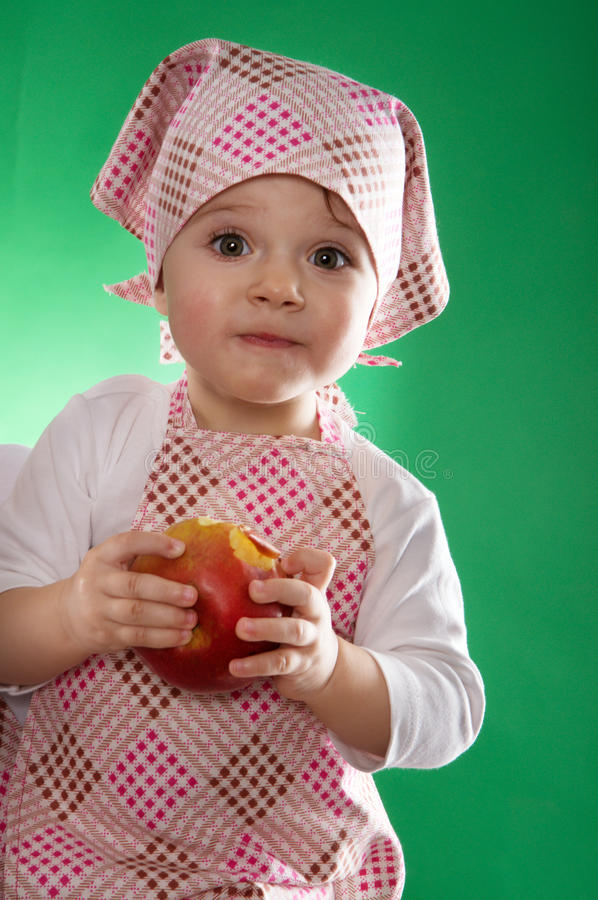 The baby girl with a kerchief and kitchen apron holding an vegetable isolated. On the green background royalty free stock photo