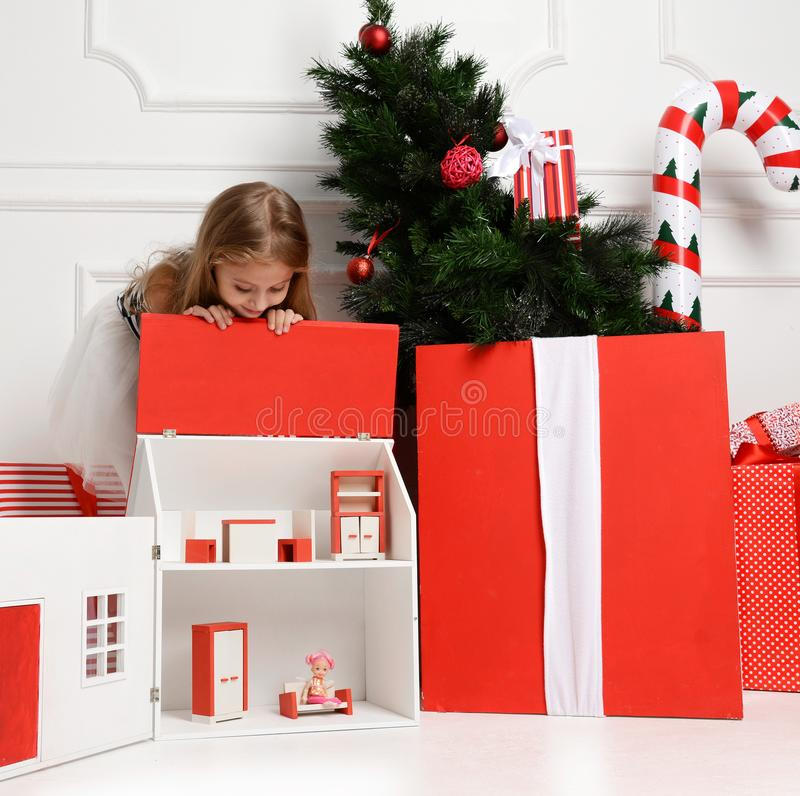 Baby Girl Kid playing with christmas red house in play room at home or kindergarten with little dolls toys royalty free stock image