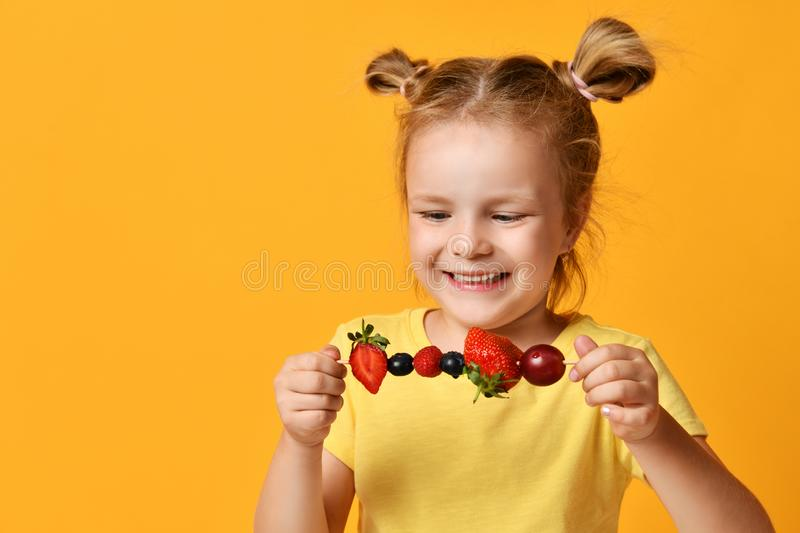 Baby girl kid in t-shirt holding smelling biting eating fresh berries cherry strawberry raspberry on skewer stock images
