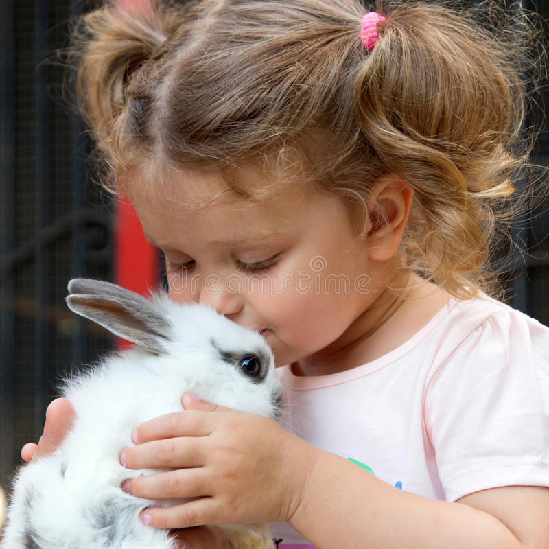 Baby girl kissing baby rabbit. stock photos