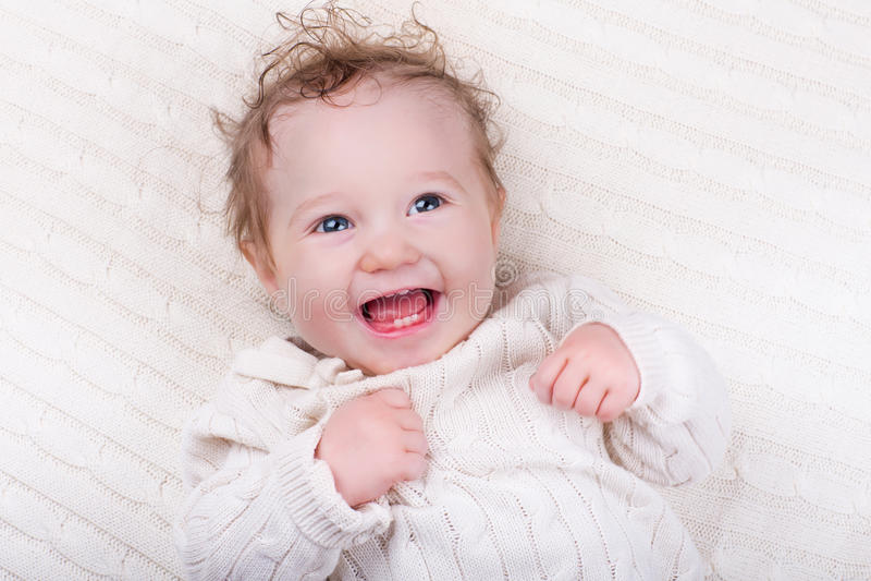 Baby girl on knitted blanket stock image