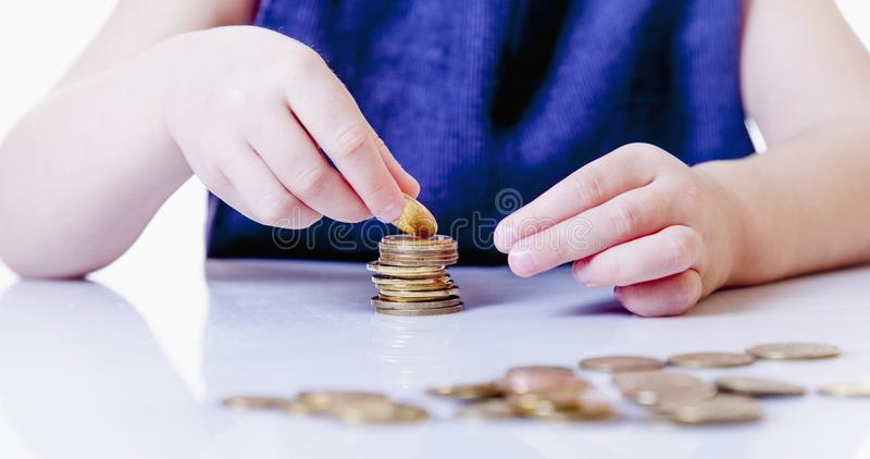 Baby girl learns to count coins money, success, business, wealt royalty free stock photo