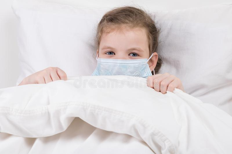 Baby girl lies ill in a white bed with a bandage on her face royalty free stock photos