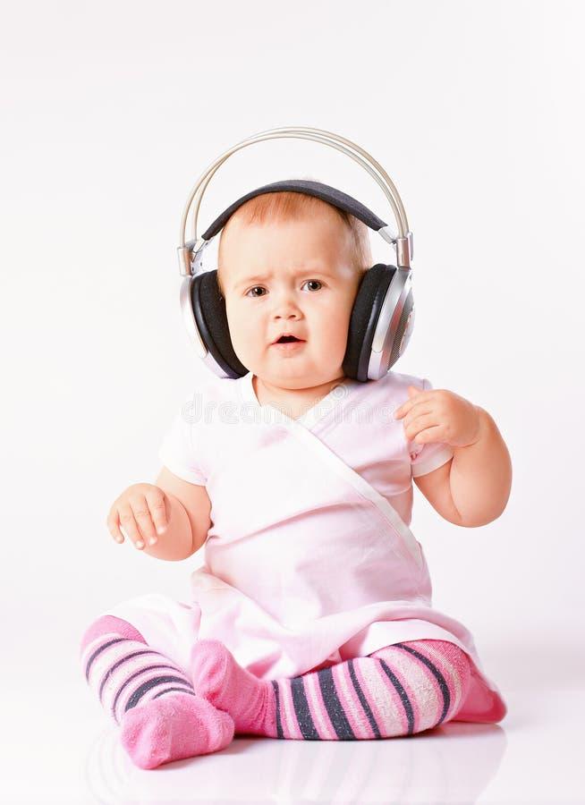 Baby girl listening music stock image