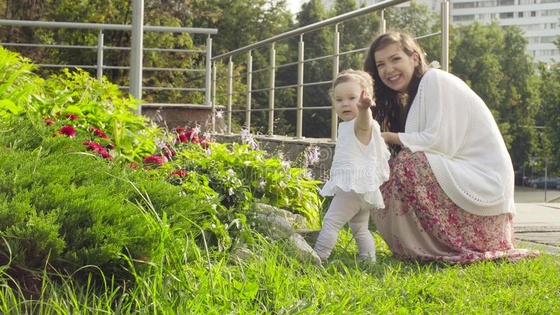 Baby girl looking on the flowers on flower bed stock photography
